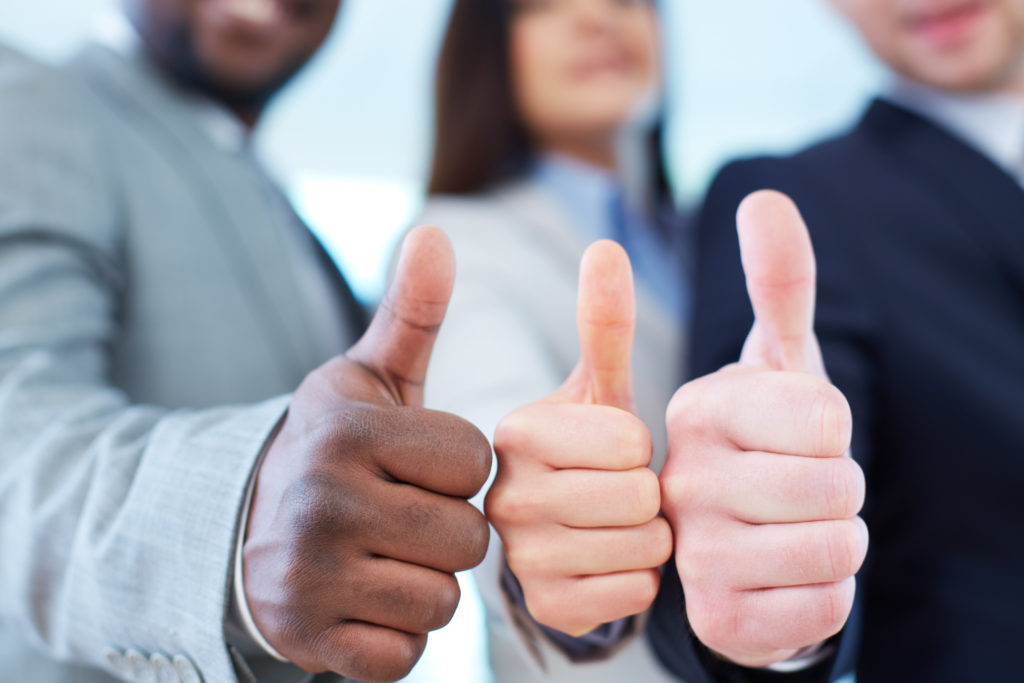 Three people with their thumbs up, representing business partners.
